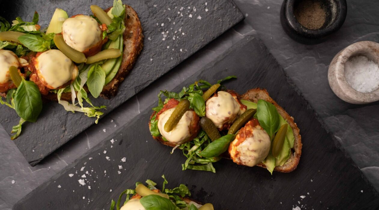 Two open sandwich with creamy coloured balls and greens on black slab, salt flakes scattered around