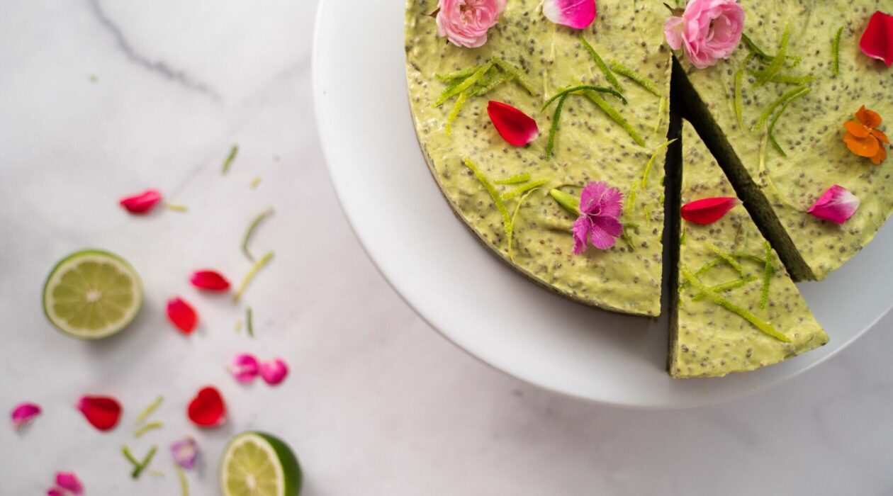 Round green cake with a slice cut topped with flowers on marble, lime halves and more flowers scattered.