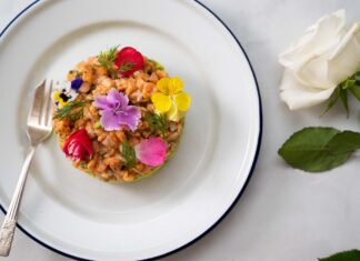 A round cake like food topped with colourful flowers on blue rimmed white round plate on marble table and a white rose.