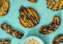 Three pineapple and four banana topped baked pies with chocolate drizzles on green table with a bowl of nuts