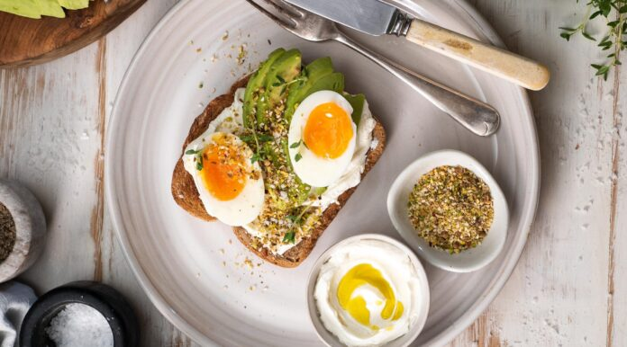 Two halves of an boiled egg, avocado slices and nutty sprinkle on toast on a white round plate with two pots of white cream 7 nutty sprinkles, fork knife on white wooden table.