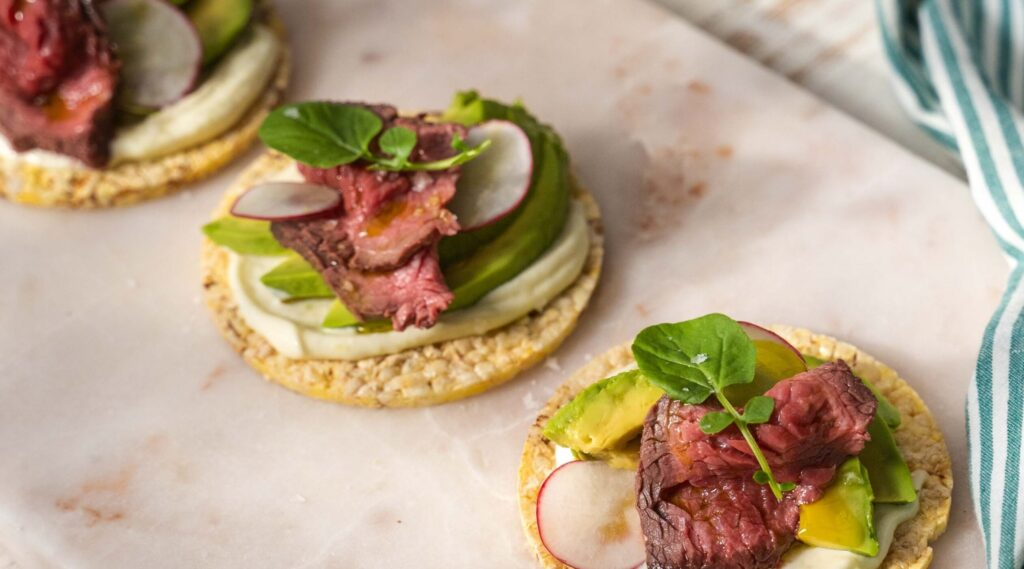 Three round biscuits topped with white cream, beef, radish and herb on top on white marble board. Green striped cloth on right side.