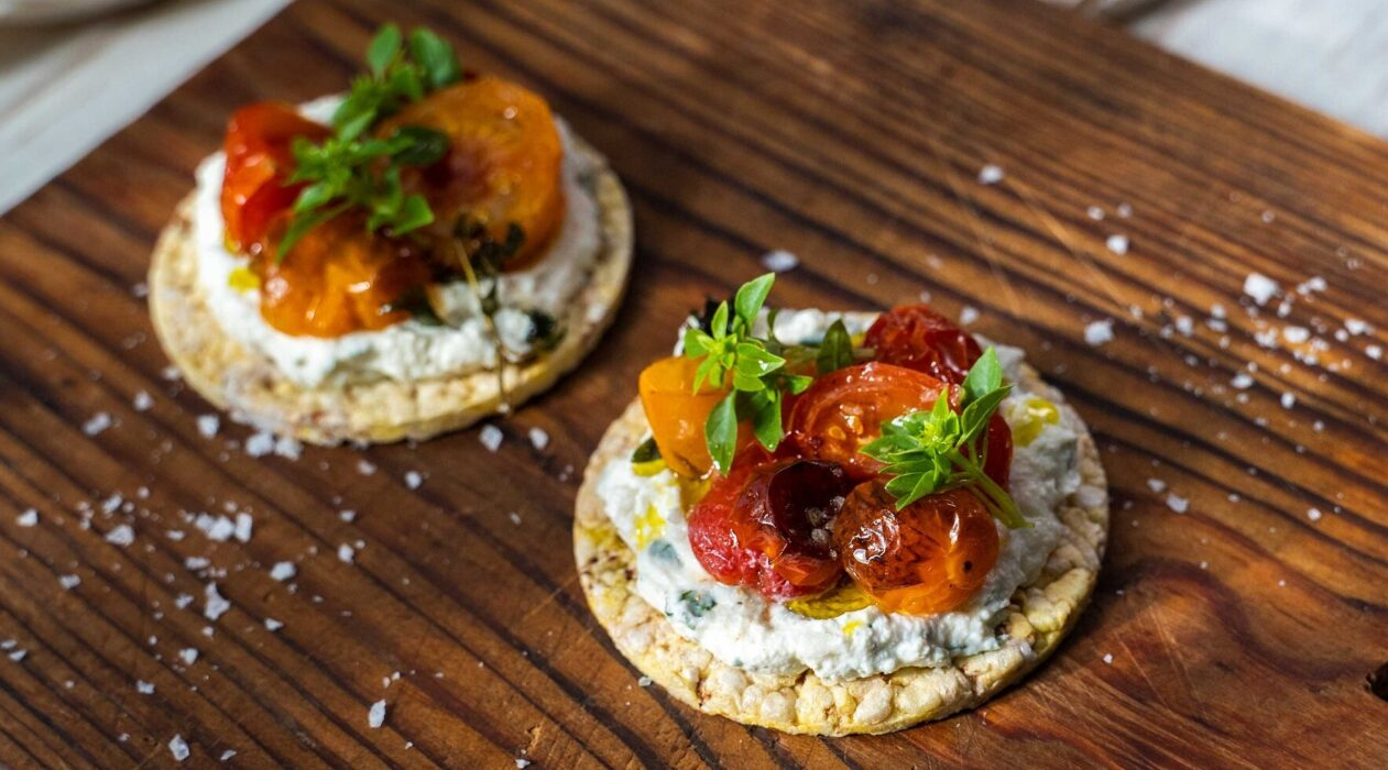 Two round biscuits topped with white cream, baked tomatoes and herbs on wooden board, salt flakes scattered around.