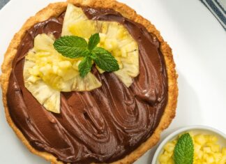 A large tart filled with chocolate cream, topped with pineapple slices and mint leaves on white board with a bowl of cut pineapples and green striped cloth on right side