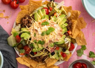 Top view of nachos with a lot of ingredients on pink back ground. tomatoes, lemon, herbs etc. scattered around the dish