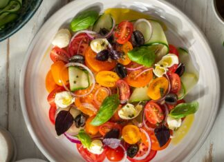 A plate of colourful tomato salad with purple green herbs on white board.