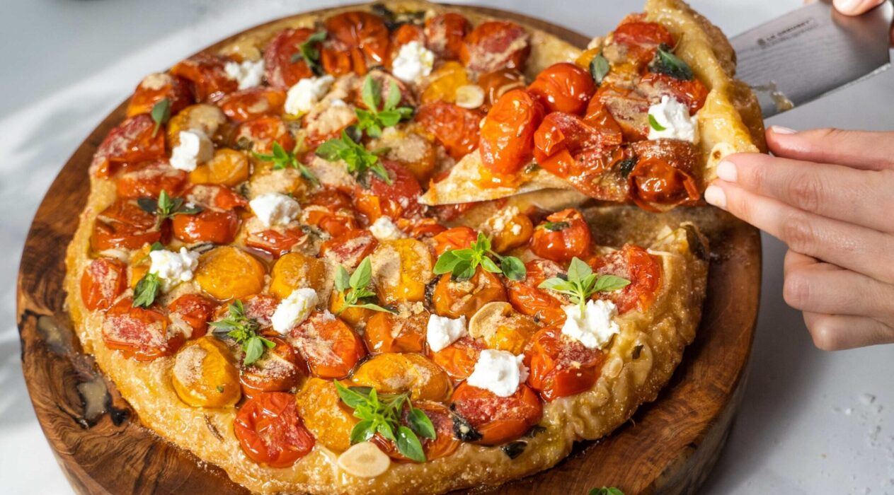 A hand and knife sliced into a round tomato tart with white cheese and green herb on wooden board.