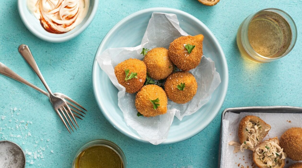 Six fried balls of food on paper lined blue bowl, each topped with green leaf. Two glasses of beer, pot of creamy sauce, two forks around the bowl and more fried balls on a tray on a corner.