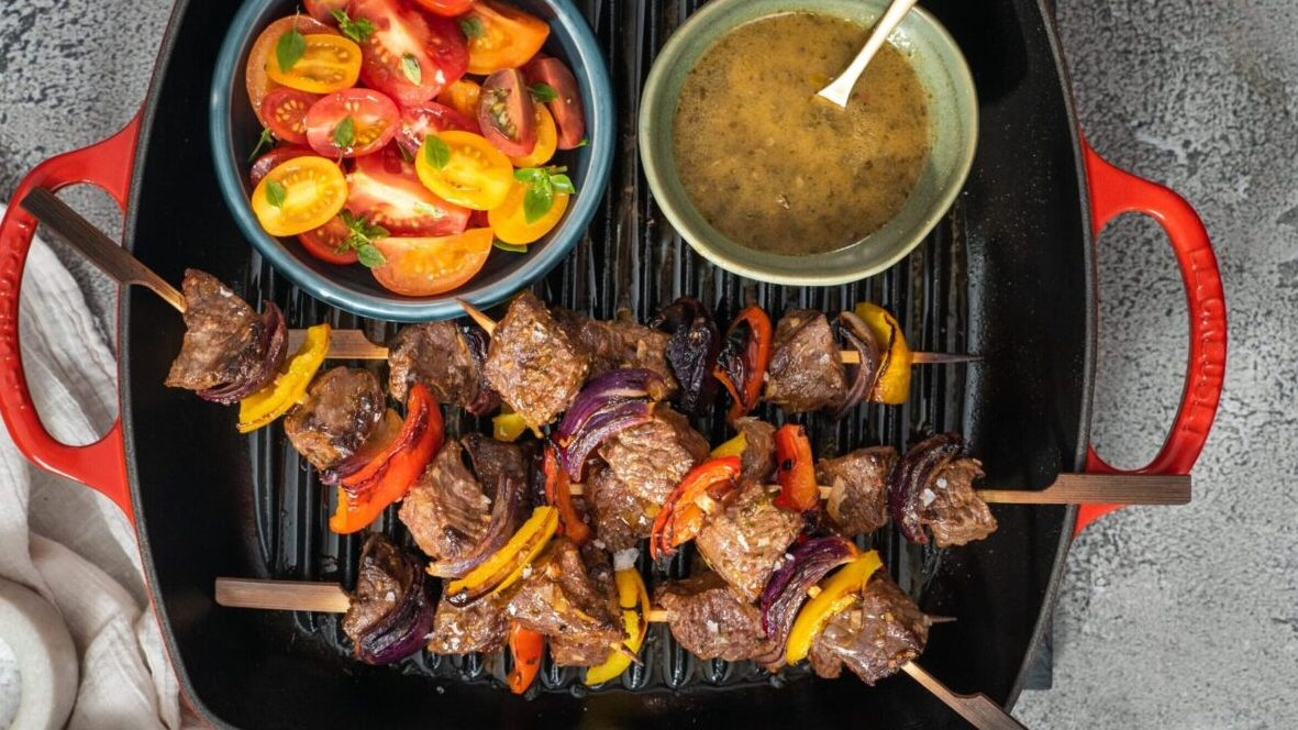 4 beef and vegetable skewers, a bowl of tomato salad and a bowl of greenish brown sauce on a red skillet with two handles.