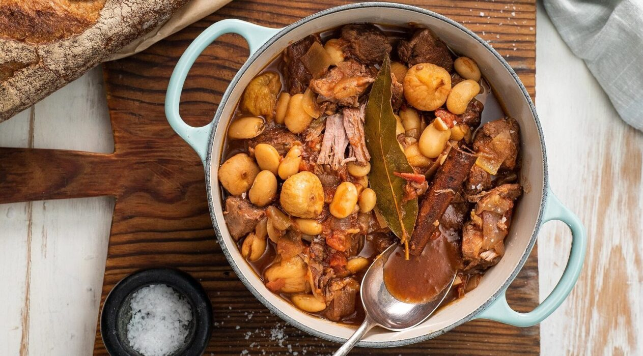 Brown meat and light brown food stew in a light blue casserole pot with a spoon on wooden board, black pot of salt, bread, gray cloth around it.
