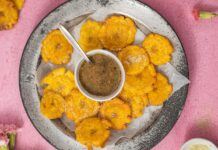 Several round snacks around a bowl of greeny brown sauce with a handle of a spoon on a metal tray on pink background. Pink flowers, pot of condiments, more snack around it.