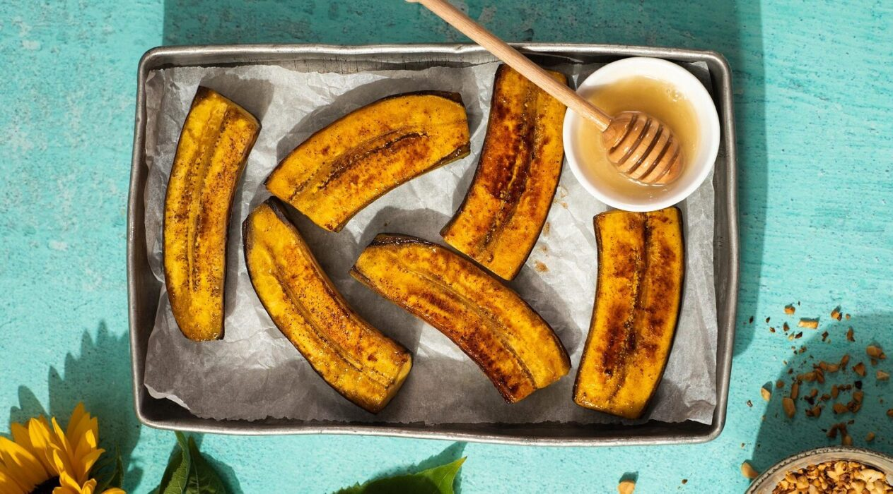 6 browned banana like food and a dish of honey with wooden stick on a metal tray on green mint green background. A sunflower and a bowl of nuts at the bottom edge.
