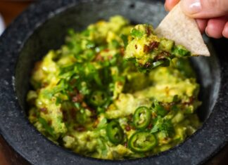 A black chunky bowl full of green creamy food topped with green herbs and chilli slices, a hand folding a piece of triangular chip digging into the food.