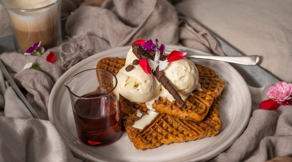 3 pieces of waffles topped with white ice-cream, chocolate and flower pettals and a jar of brown liquid on a white round plate on cloth with a cup of drink