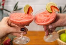 Two hands holding a glass of pink slushy drink each, decolated with lime and strawberry slices, limes, tree blanches with red berries in background