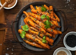 Cooked whole baby carrots on a round black skillet on wooden board, pots of honeyand white and black sesame seeds