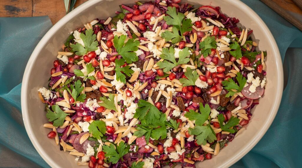 An oval platter full of colourful vegetable salad on blue cloth on board.
