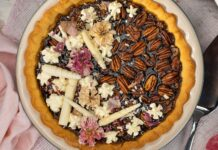 Top view of a round pecan pie topped with white and pink decorations on pink cloth, punk dried flower and a silver cake slice on right side of the pie.