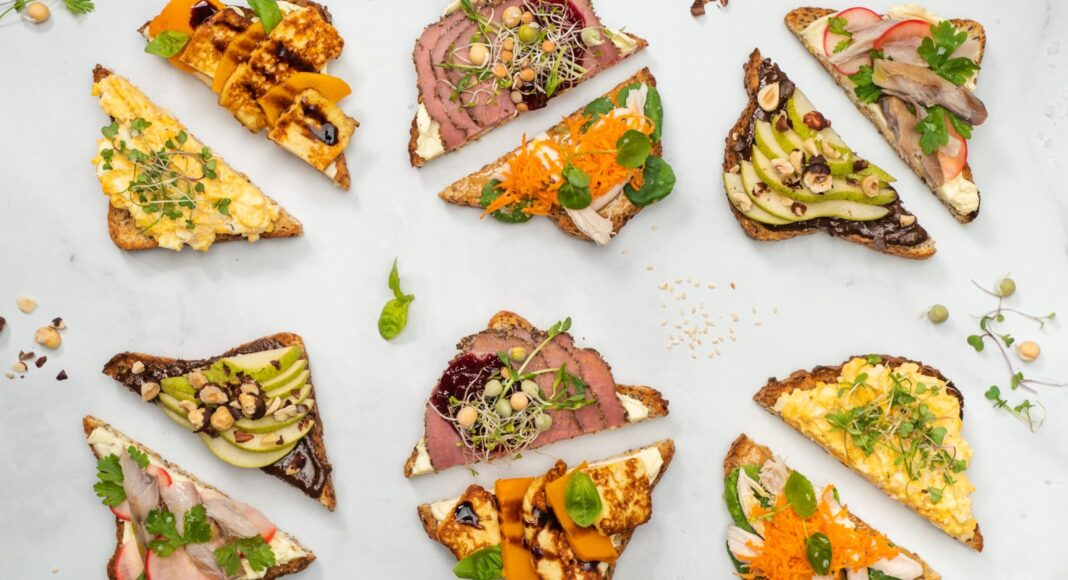 12 triangular open sandwiches with various toppings on white marble board.
