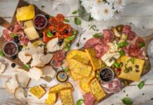 Assorted meat, cheese, bread, pots of brown food arranged on two wooden boards and a vase of white flowers.