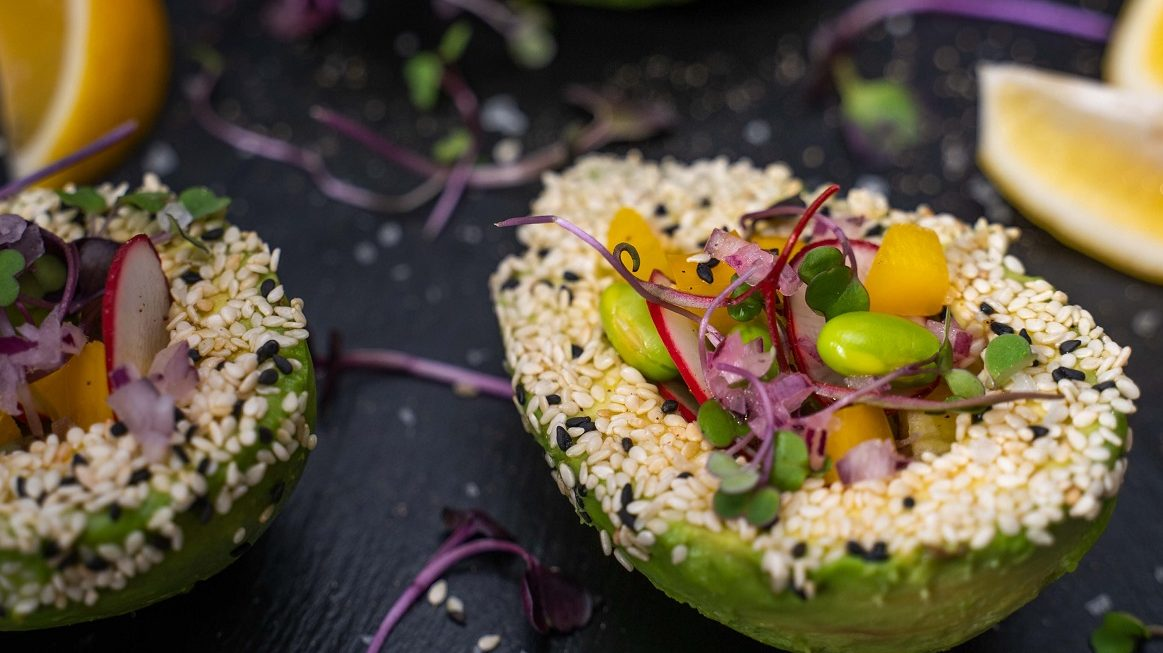 Two halves of avocado filled with colourful salad, topped with seeds on stone slate with lemon wedges.