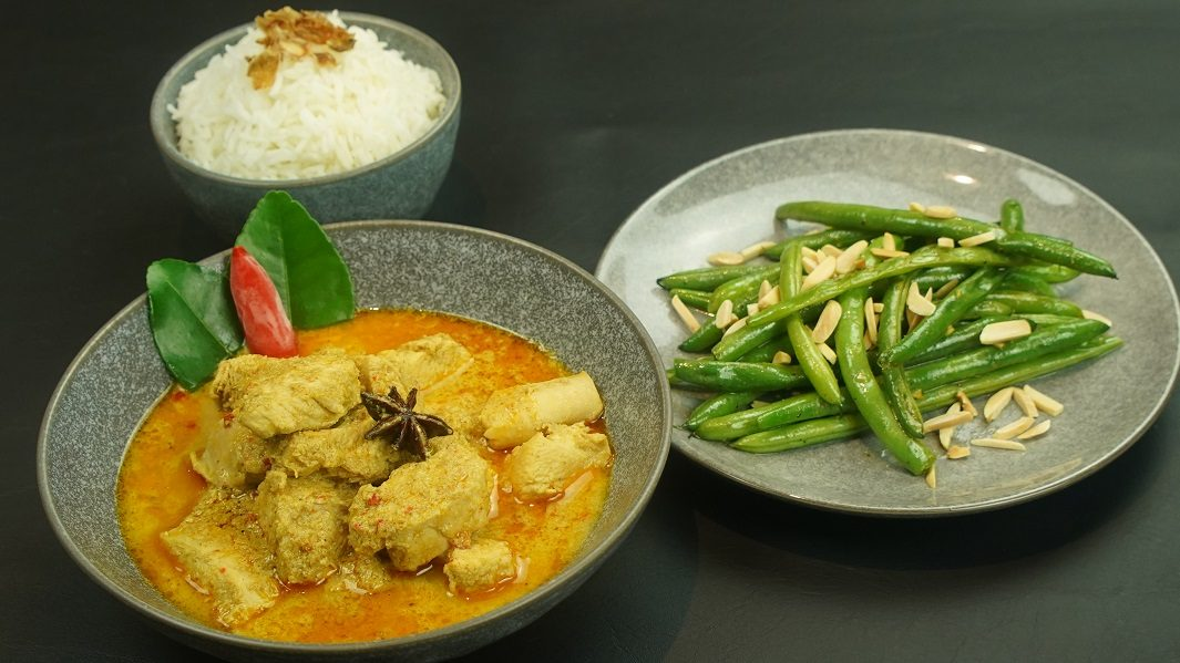 A bowl of coconut chicken curry, a plate of green beans and a small bowl of white rice on dark grey table.