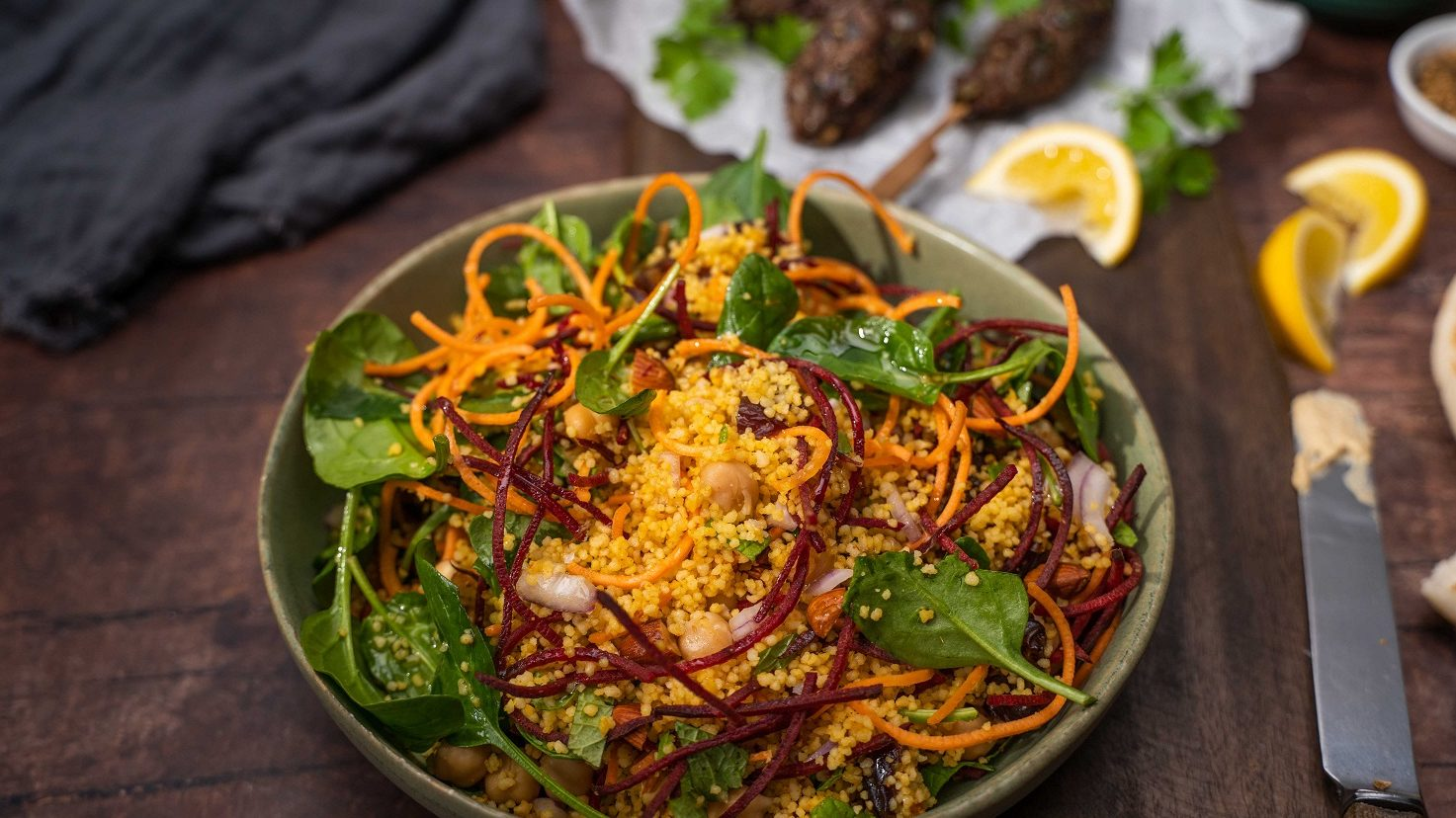 A bowl of yellow grains, red and orange strips and green leaf salad, meat kebabs and lemon wedges in the back.