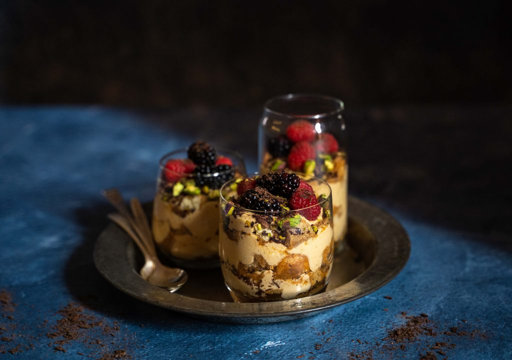 3 berry tiramisu glasses with spoons on a plate on a dark blue background