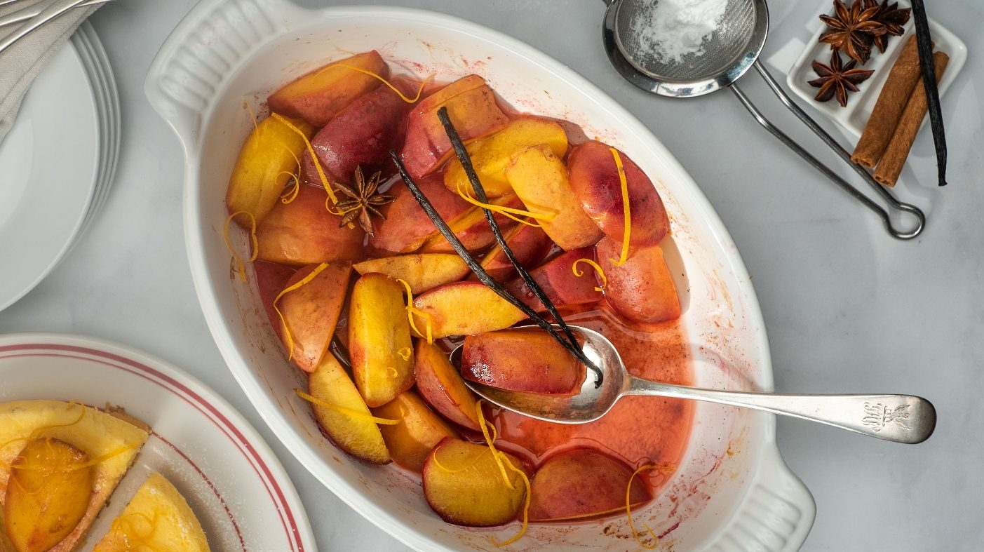 A white oven dish full of orange red coloured baked fruit wedges with a sliver fork, spice on small plate and a tea strainer at side.