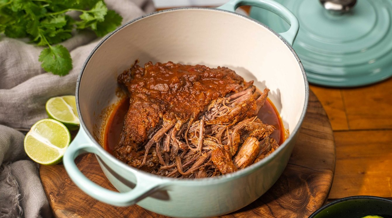 A pale green casserole dish with cooked meat in red-brown sauce partly pulled in it on wooden board. two halves of lime, green herb and the lid of the dish in background.