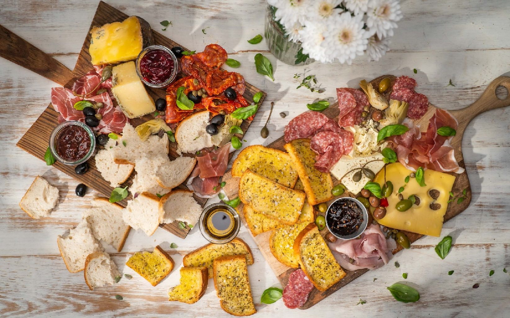 Two wooden board topped with cheeses, deli food and bread with bunch of white flowers
