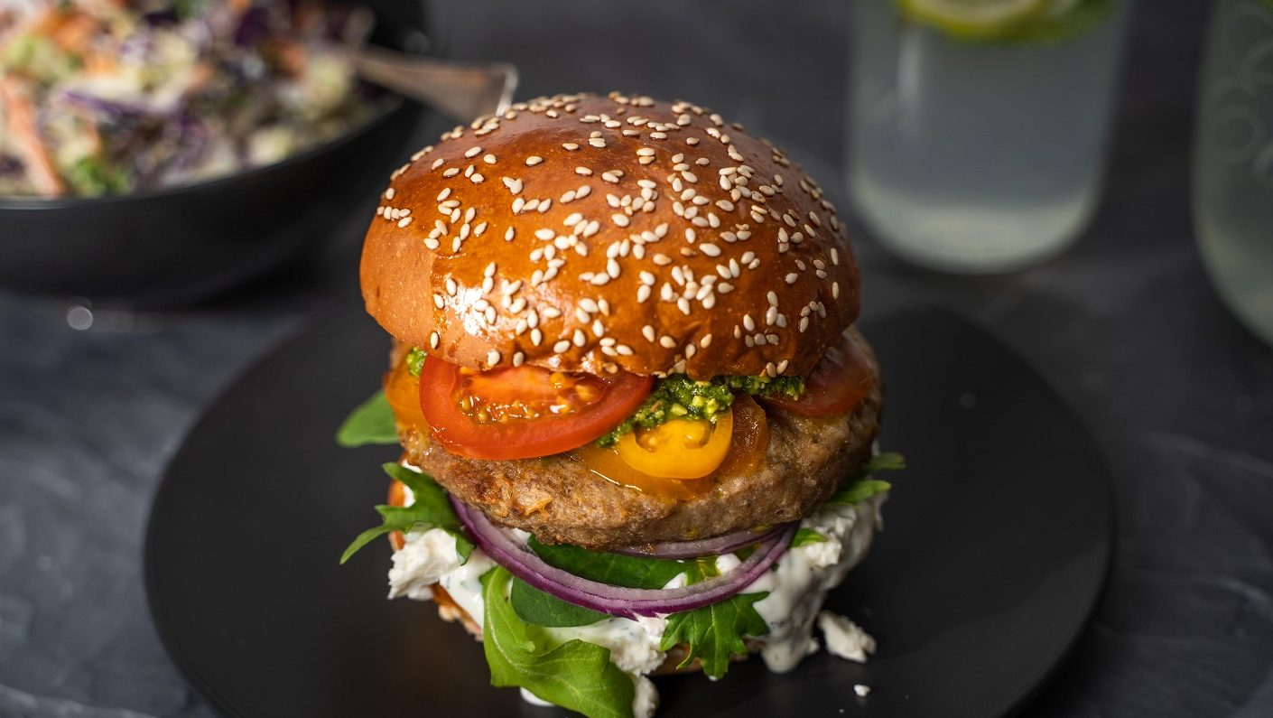 A big burger with green lettuce, white sauce, red onion, pattie, sliced tomatoes in filling on a black round plate. A bowl of coleslaw and glasses of drinks in the back.