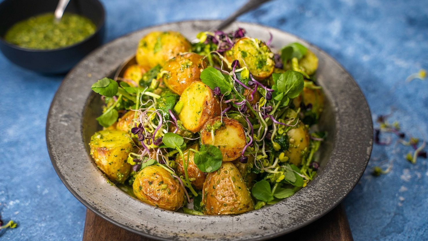 A heap of potato, micro shoots and greens salad on a metal plate with a black bowl of green sauce on blue table.