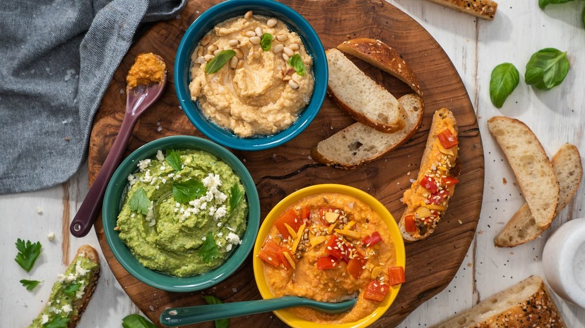 Tree bowles of light brown,green and orange coloured hummus and slices of bread on wooden board