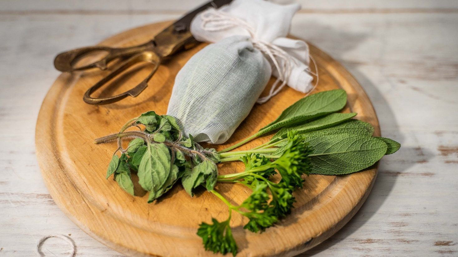 Some green herbs, a pair of scissors and a white parcel on round wooden board.