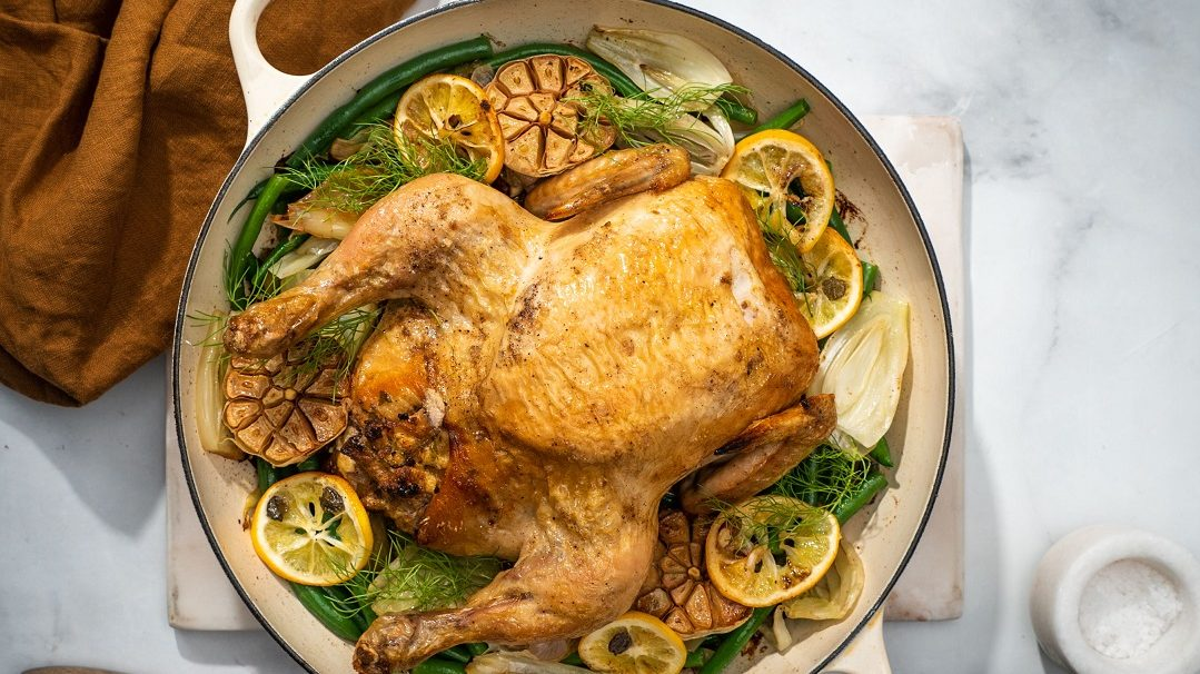 A roasted whole chicken in a round pan with lemon slices and greens under it, brown cloth on top left of the pan