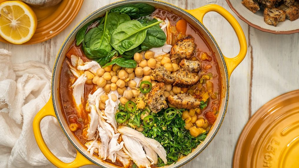 A yellow pot of soup with chicken, chickpeas, croutons and greens.