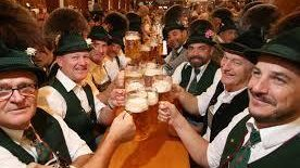 Men in lederhosen and hats sitting on long table cheering with beer mugs