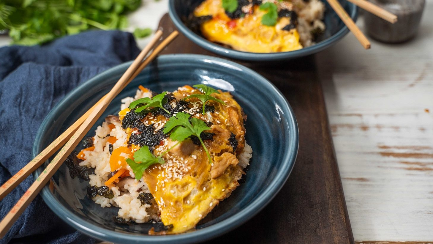 Two dark blue bowls of rice topped with egg, herb and nori, and chopsticks.
