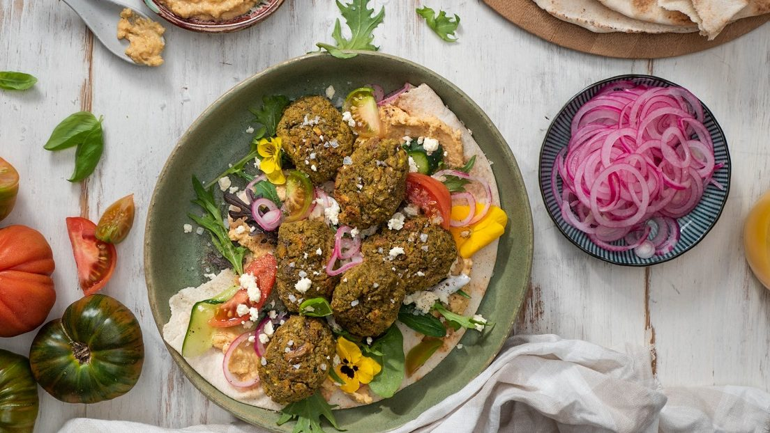 A plate of brown falafel balls on flatbread and red yellow capsicums, a plate of sliced red onions, tomatoes, flatbread around it.