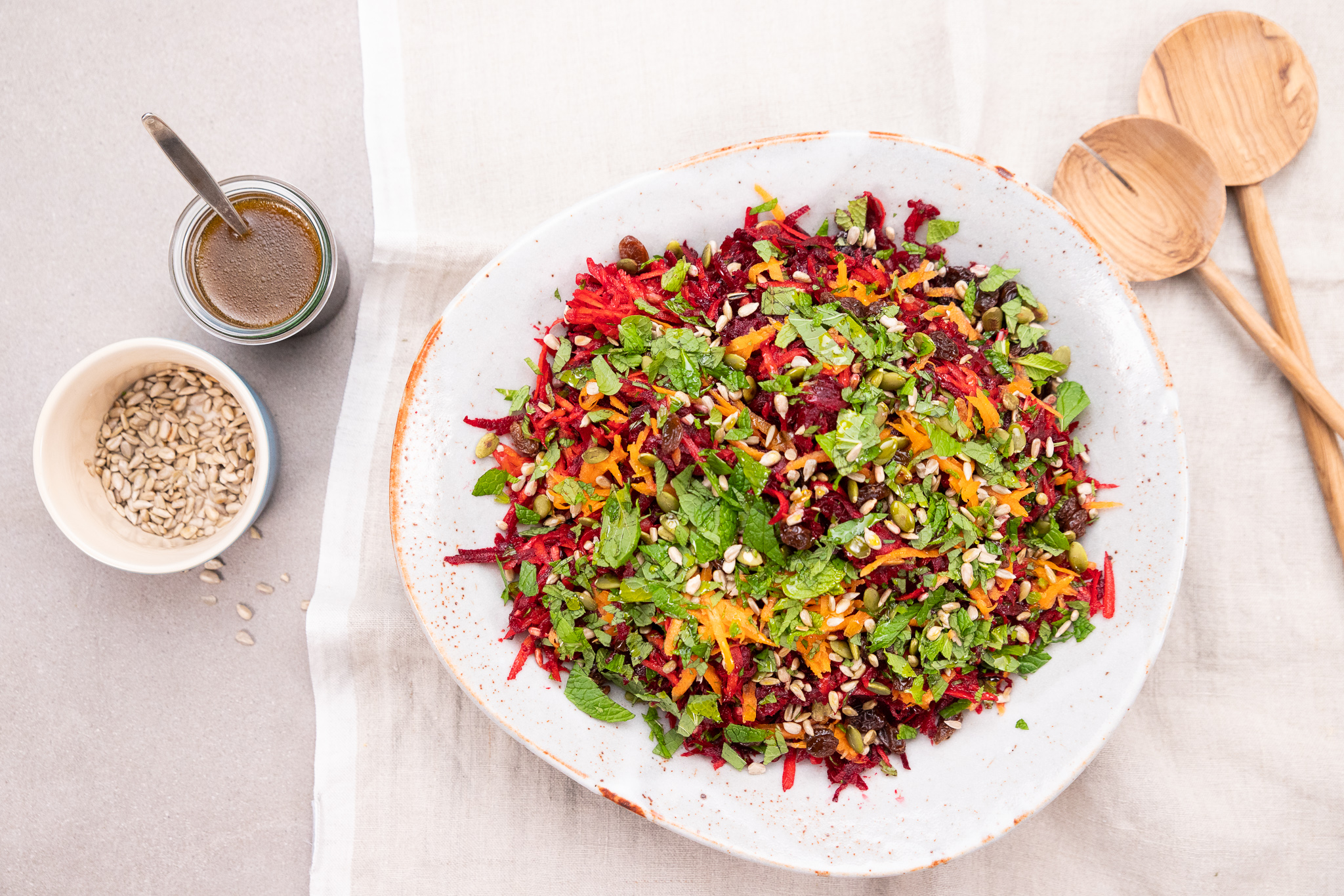 A colourful salad with greens carrot and beetroot sits on a white plate on a napkin