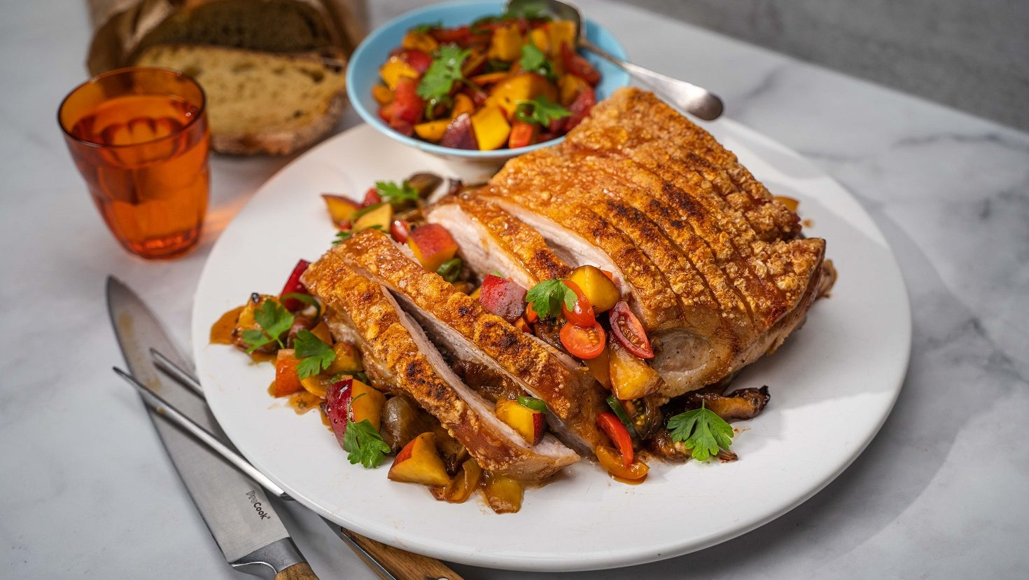 A roast pork topped with colourful fruit salsa, and a small bowl of salsa in the back