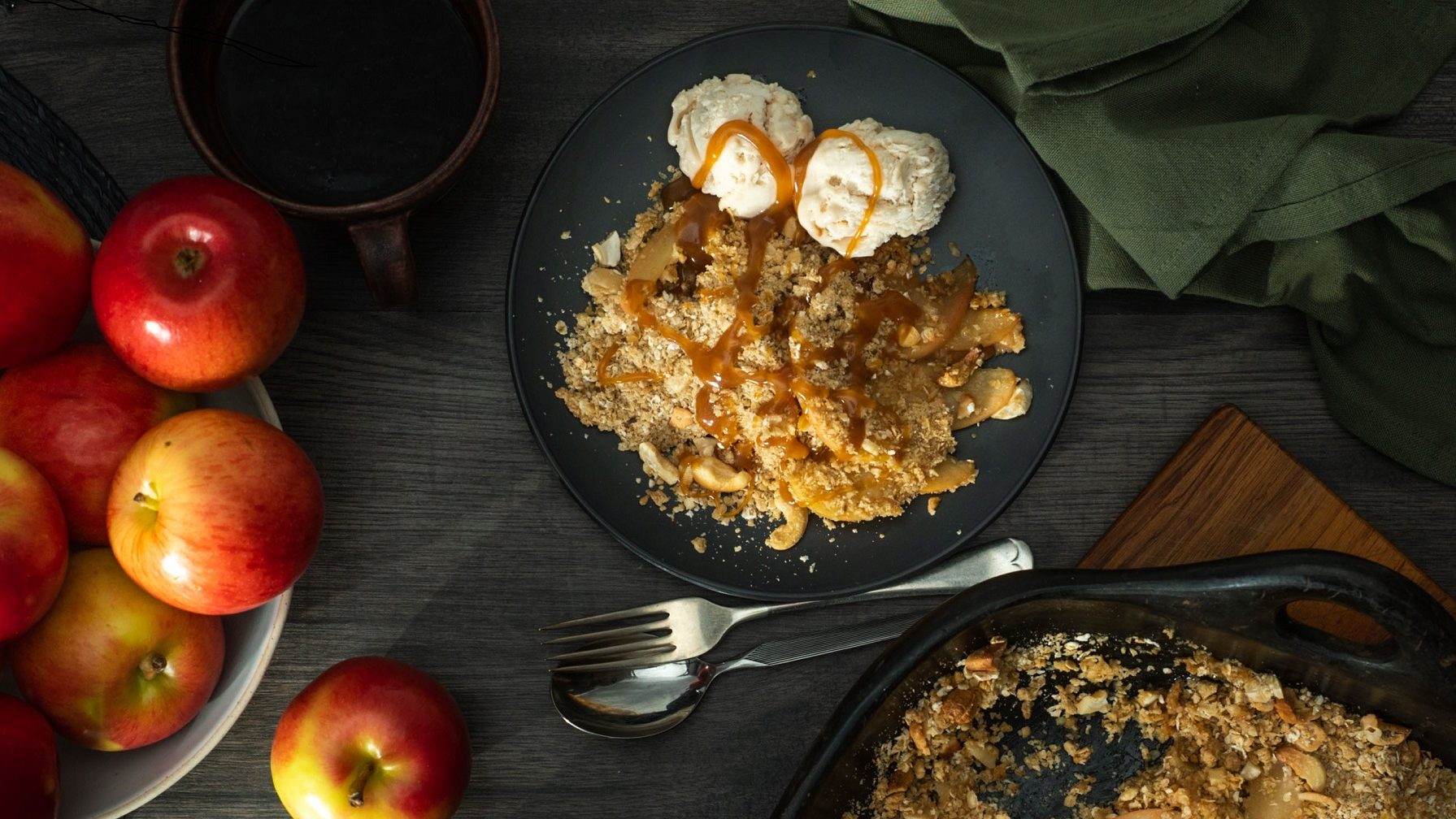 Several red apples in a bowl on left, brown crumble with two scoops of ice cream drizzled with brown sauce on blue plate in middle and black baking dish with crumble on right.