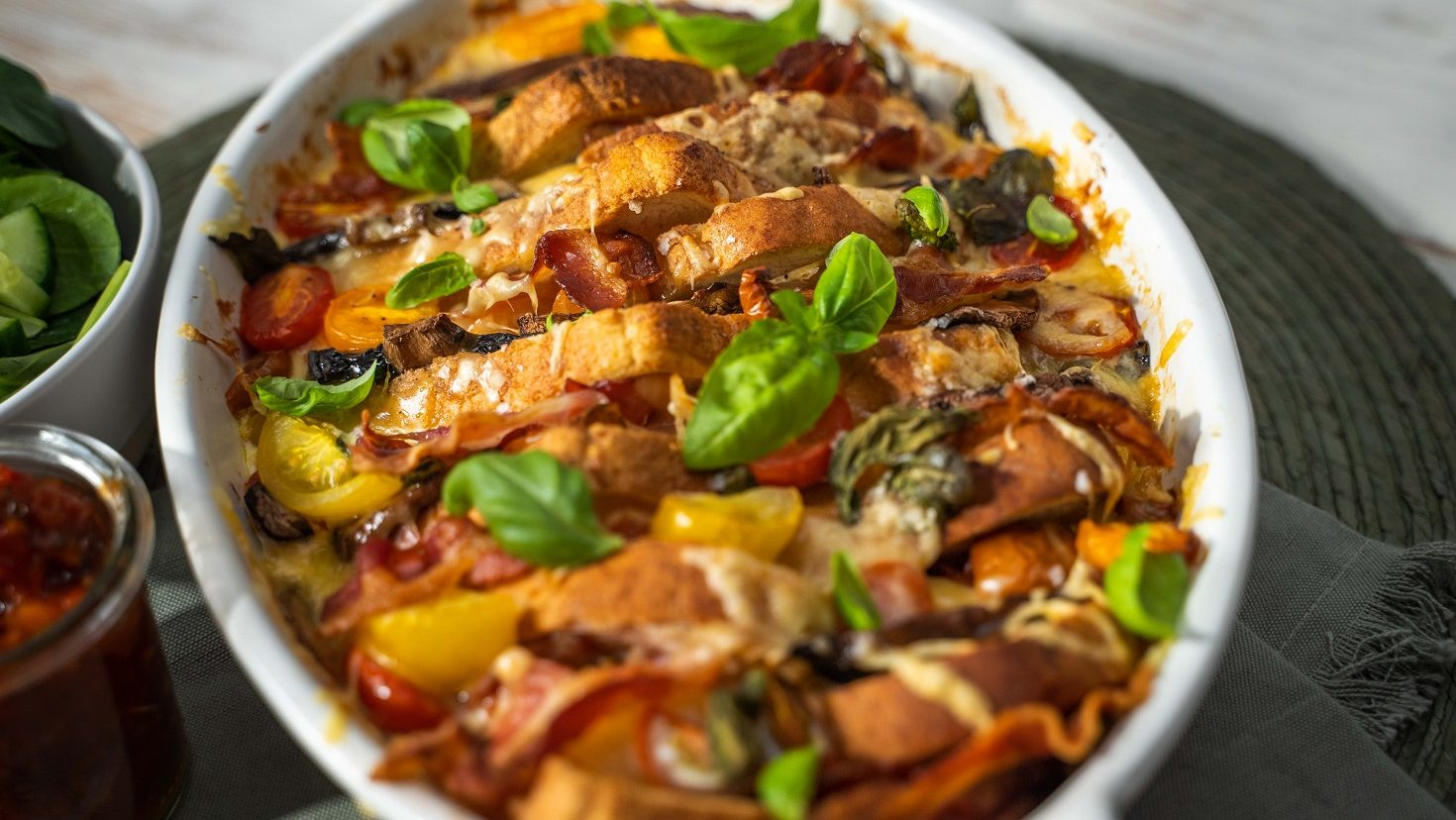 A white oven dish full of bread, bacon, tomato, mushroom bake topped with basil leaves.