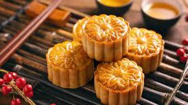 5 mooncakes on bamboo tray with chopsticks and red berries