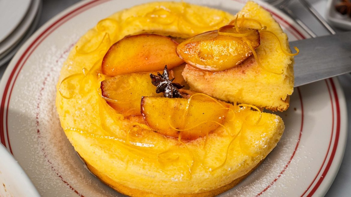 Yellow round cake topped with cooked peaches and citrus rind, a slice being taken out on metal cake server.