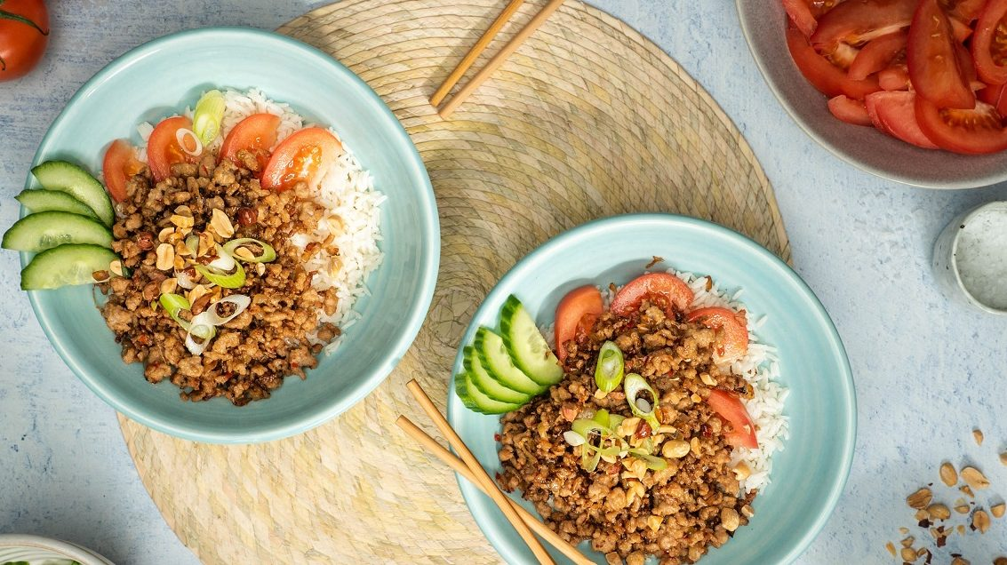 Two blue bowls of meat, tomato and cucumber on rice on a round light brown mat with chopsticks. Tomatoes and nuts around them.