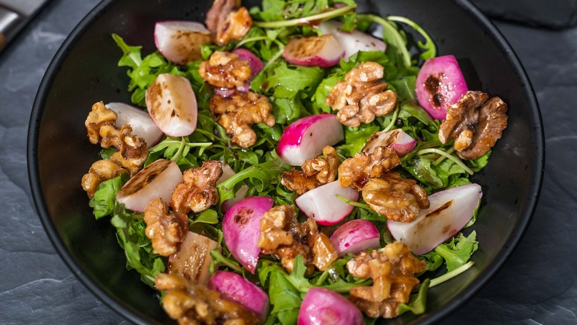 Close up of red radish, walnuts and green salad in a black bowl.