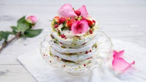 Layered meringue cake with pistachio, pink roses and berries on a cake stand