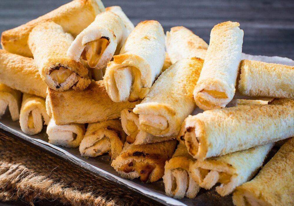 Pile of white bread cheese rolls on a platter